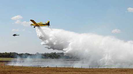 AERIAL SUPPORT: A water bomber dumps its load on the fire burning in a paddock owned by Lyndhurst Stud.