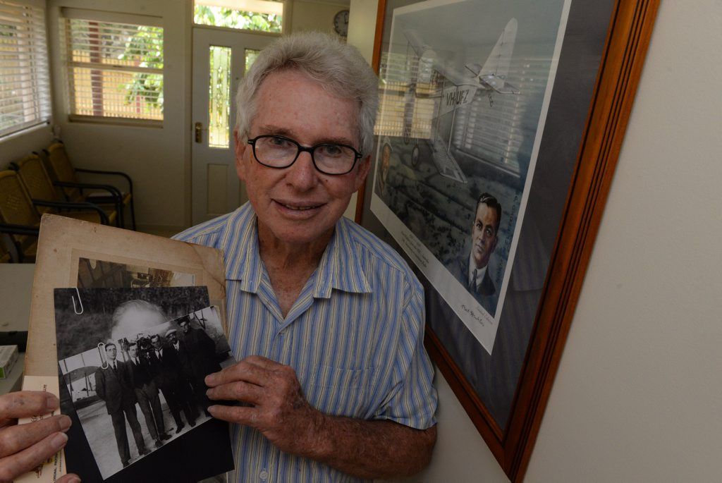 BERT HINKLER: Lex Rowland holding a photograph showing Bert Hinkler (centre) and his mechanic (far right). Photo: Mike Knott / NewsMail