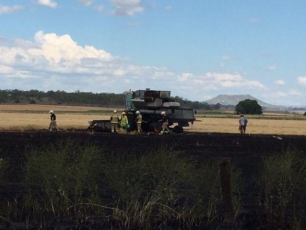 Emergency servicez investigate a fire which destroyed a header in a paddock beside Oakey Biddeston Rd at Aubigny.