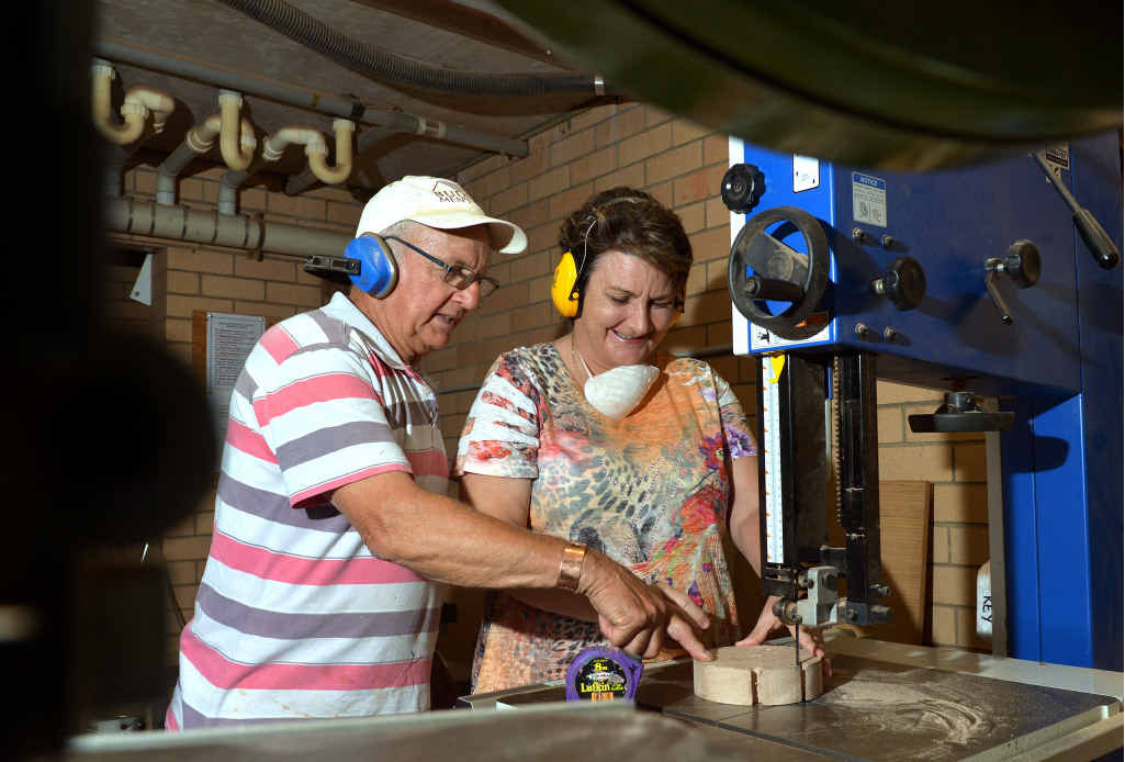 A WOMAN IN A MEN'S SHED? Yes, Graham Down of Buderim Men's Shed teaches Leona Johnson how to handle a bandsaw.