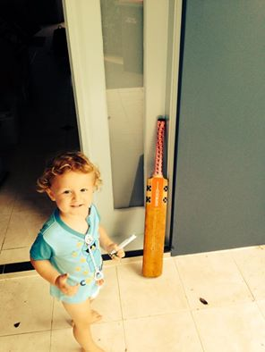 Young Myles helped his dad place a cricket bat at the front door in memory of Phillip Hughes.