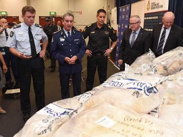 Senior police and customs officers inspect some of the seized drugs in one of the largest drug busts in the country's history, worth up to 1.28 billion USD, in Sydney on November 29, 2014. Australian Federal Police said six men were charged over their involvement in the attempted importation of almost three tonnes of MDMA and crystal methamphetamine, also known as ice, into Sydney.