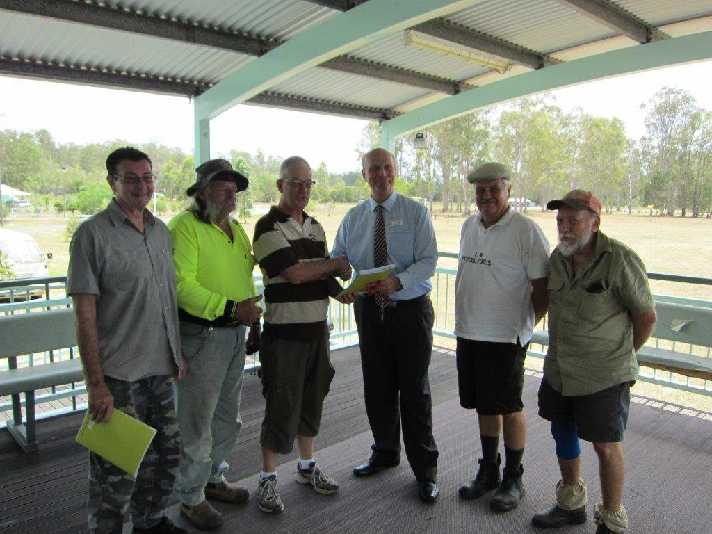 Community resilience portfolio councillor Rolf Light (wearing tie) hands over a copy of the Community Co-ordination Committee Handbook to Richard Sibraa, Thomas Schwartz, John Greenaway, John Davis and Gary Gorely from the Glenwood Community Co-ordination Committee.