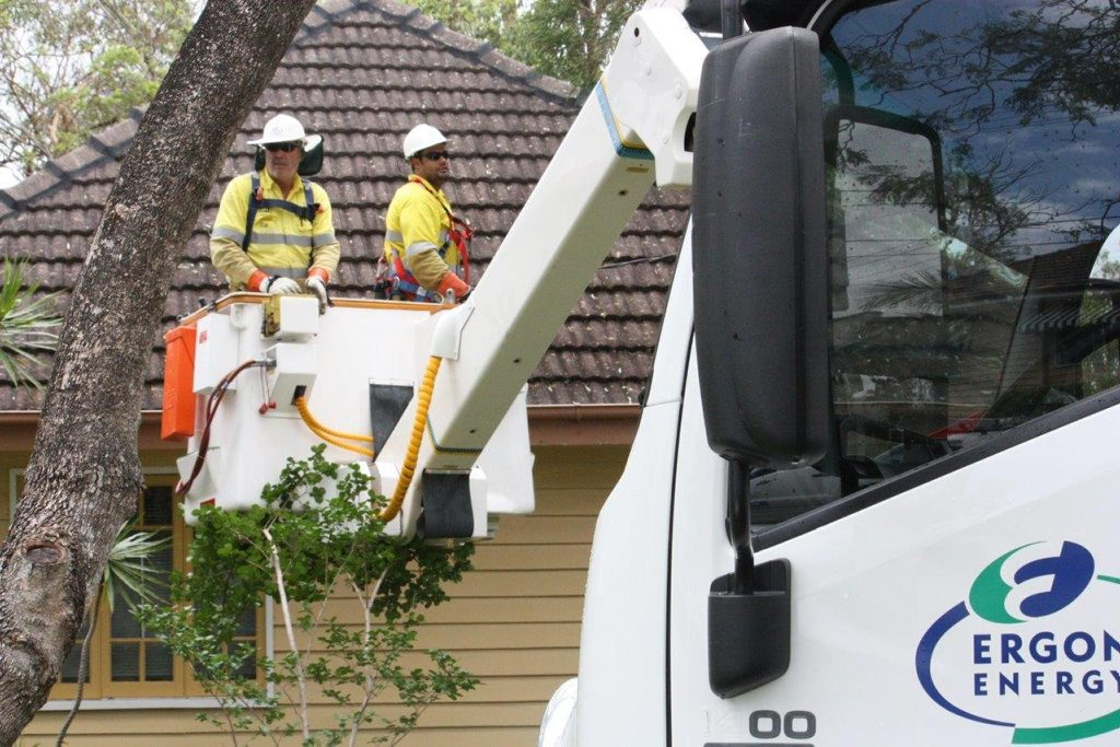 Ergon Energy Toowoomba crew members Dan Flegerbein (left) and Nathan Simpson assist with the restoration of power in St Lucia after storms ripped through Brisbane.