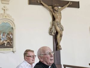 Father Ray Johnston and Father Tom Keegan with the cross taking new position in the re-modelled Holy Name Church.