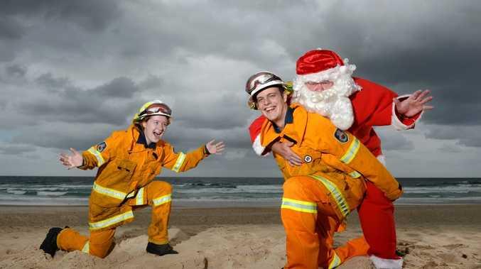 Tara Goswell and deputy captain Joshua Farrell of the Tweed Coast Rural fire brigade with Santa at Cabarita Beach. Photo: John Gass / Tweed Daily News