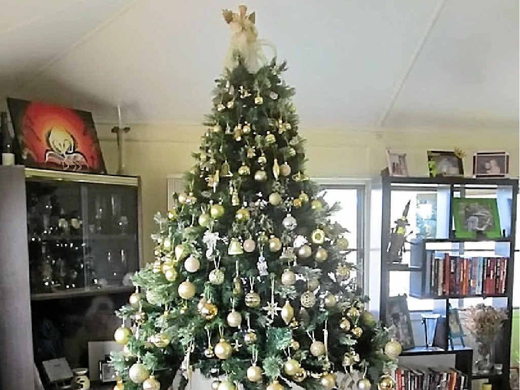 Kylie Bulley's Christmas tree is adorned with gold decorations and surrounded by a train track and larger ornaments.