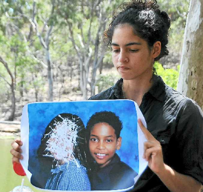 SCARRED: Domestic violence has cost Matilda Gilbert both her mother and her brother. She holds a school photo of herself and brother Horace, destroyed by her mother Roxane during a fit of anger.