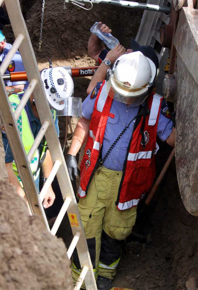 Emergency services staff speak to the patient in the trench, which is about three metres deep.