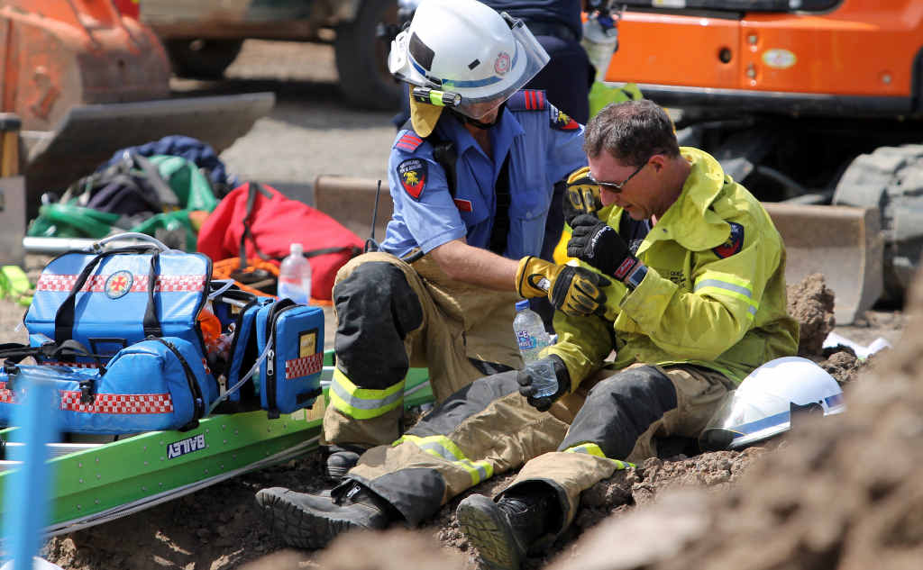 DIFFICULT SCENE: Firefighter Michael Gagnepain is offered water after working in the trench conveying medical supplies.