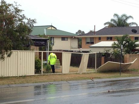 A police officer carrying a panel of iron fencing into a yard a Torquay after it was blown away in a storm.