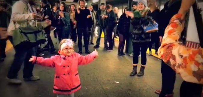 A little girl inspires a subway platform, dancing to a busker's music.
