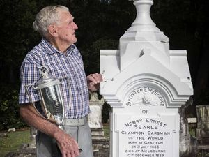 LEFT: Lex Essex, next to the grave of Henry Searle, holds on to the Bill Beach NSW Station Championship he won for rowing in 1956. PHOTO: ADAM HOURIGAN