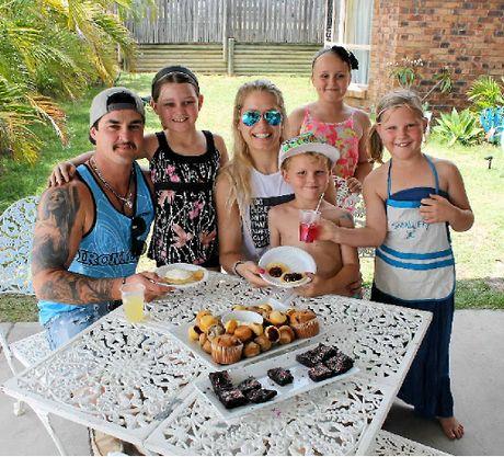 YOUNG ENTREPRENEURS: Paying customers Justin Orchard and Emma Slatter with kids' lawn cafe creators Ashley Slatter, Jorja McGennan, Cooper Slatter and Bree Slatter.