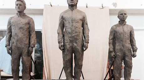 The statue of Julian Assange stands between sculptures of Edward Snowden, left, and Chelsea Manning
