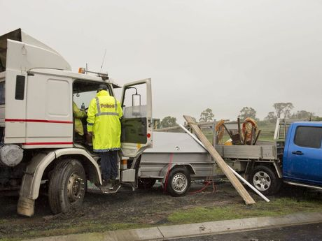A runaway semi-trailer comes to a stop against a tradie's ute.