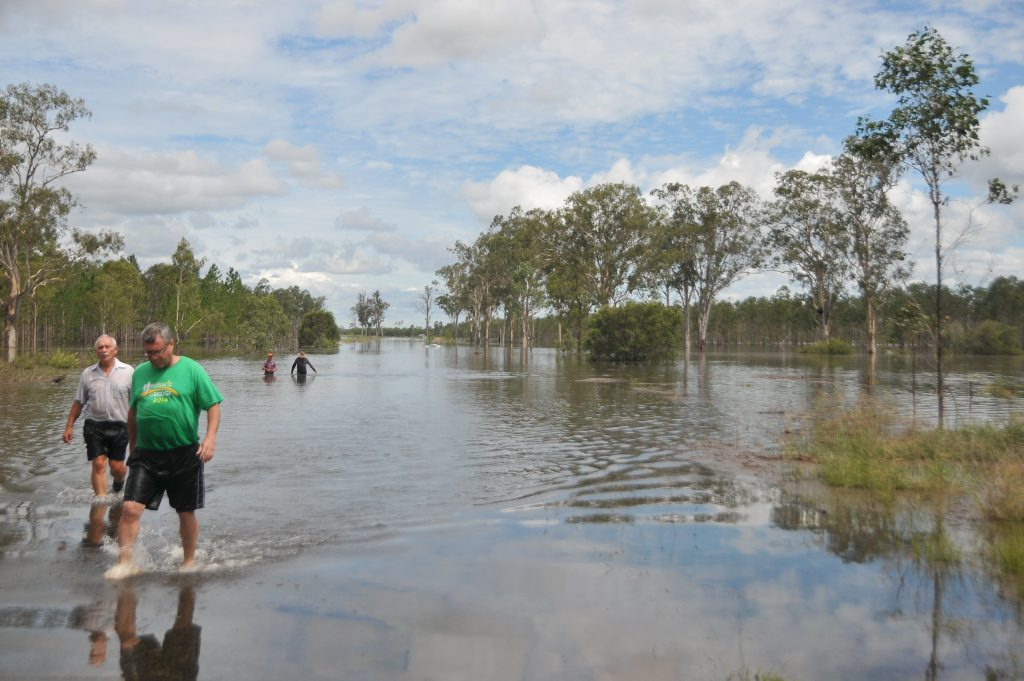 A passenger and Miriam Vale police senior sergeant Owen Harms wading back from the second car that was lost in flood water on Fingerboard Rd on Friday.