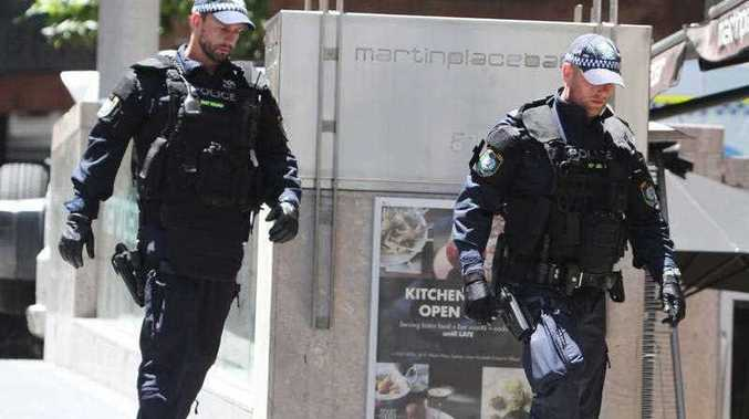 Police check buildings close to a cafe under siege at Martin Place in the central business district of Sydney.