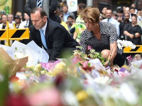 Prime Minister Tony Abbott (L) and his wife Margaret lay wreaths at a makeshift memorial near the scene of a fatal siege in the heart of Sydney's financial district on December 16, 2014. Sydneysiders including tearful office workers and Muslim women in hijabs laid flowers at the scene of the deadly siege, in an outpouring of grief and shock that this could happen in their easy-going city. AFP PHOTO/Peter PARKS