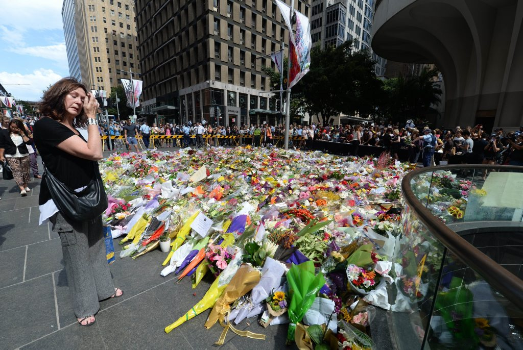 A visitor looks at a makeshift memorial near the scene of a fatal siege in the heart of Sydney's financial district on December 16, 2014. Sydneysiders including tearful office workers and Muslim women in hijabs laid flowers at the scene of the deadly siege, in an outpouring of grief and shock that this could happen in their easy-going city. AFP PHOTO/Peter PARKS