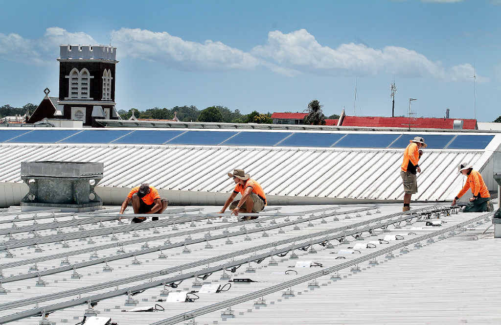 Workers from Watkins Electrical, Jaden van Tonder, Henrico van Tonder, Ben Cook and Brodie Smith begin the process of laying 400 solar panels on the roof of Station Square.
