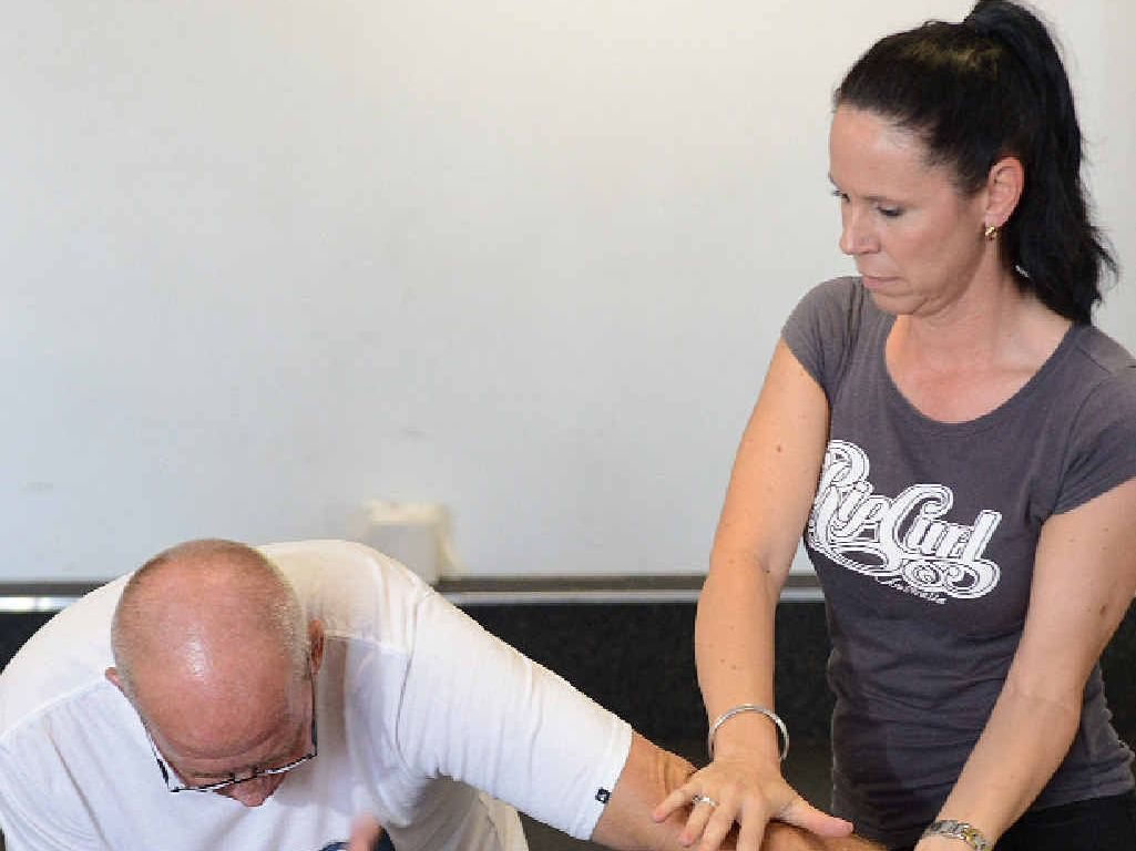 GIRL POWER: Acting Senior Constable Debbie Wruck (right) works self-defence moves on instructor Paul Baldwin.