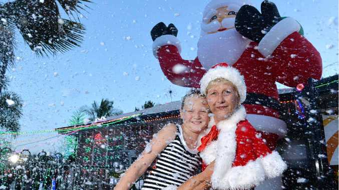 WHITE CHRISTMAS: Emma Stewart gives a hug to Dealia Walsh whose display was judged winner of this year's Christmas Lights Competition.