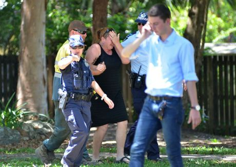 Police comfort a distressed woman at the scene where eight children aged between 18 months and 15 years were found dead.