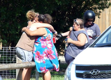 Distraught locals embrace at the scene after eight children were found stabbed to death at a house in Manoora near Cairns, Friday, Dec. 19, 2014. Eight children, aged between 18 months and 15 years, have been found dead in a house in Cairns, with a woman believed to be their mother in hospital with stab wounds. (AAP Image/Romy Bullerjahn) NO ARCHIVING