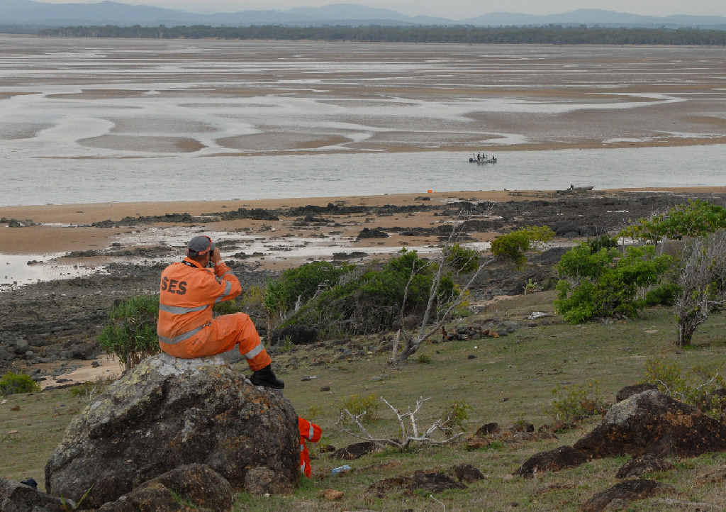 STILL SEARCHING: Mackay SES volunteers Damien Wood and Rik De Meer (on the ground) keep an eye out for signs of missing man Neville Ohl as the police boat searches at Notch Point.