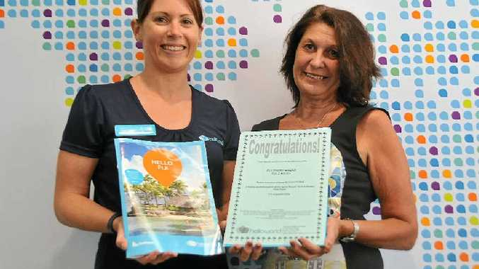 FIRST BIG WIN: Carmen Ward from helloworld Gladstone presenting Michele Archay with her free holiday to Fiji.