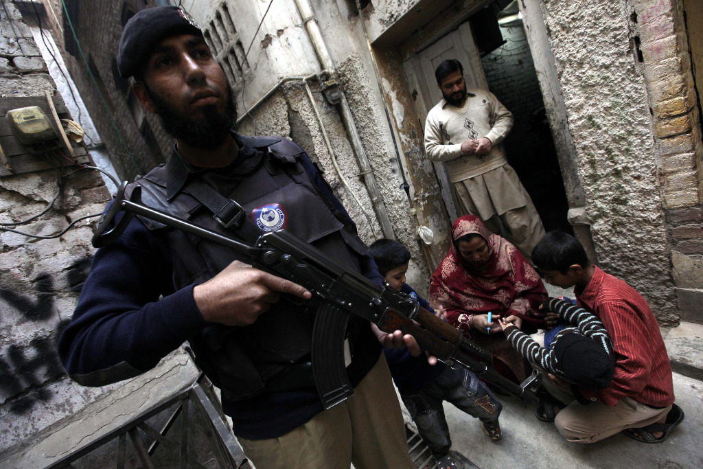 A member of the Pakistani security services stands guard while a health worker administers a polio vaccine to a child, in Peshawar, Pakistan, 20 December 2014. More than 65 polio worker and security personnel have been killed by the militants, according to Health Minister Saira Afzal Tarar. Extremists claim the vaccination campaign is a cover for a plot to sterilize Muslims.