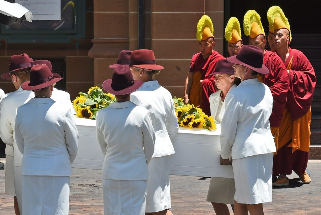 Buddhist monks pray as the coffin of Sydney siege victim Tori Johnson is placed in a hearse after a funeral service in Sydney.