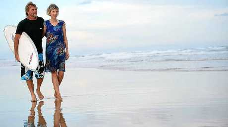 TOGETHER: Elisabeth Auffenberg and Adam Smith on Peregian Beach with the surf board that helped to save their lives in the 2004 Boxing Day tsunami.