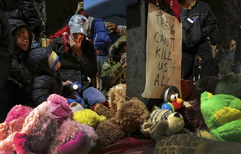 Courtney Palmer, center left, a cousin of Antonio Martin, mourns the loss at a growing memorial in a gas station parking lot in Berkeley, Mo., Wednesday, Dec. 24, 2014.