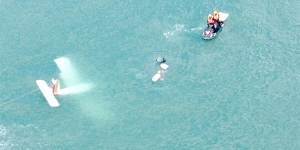 Coastguard, surfers and police secure the light aircraft which crashed into Raglan Harbour yesterday.