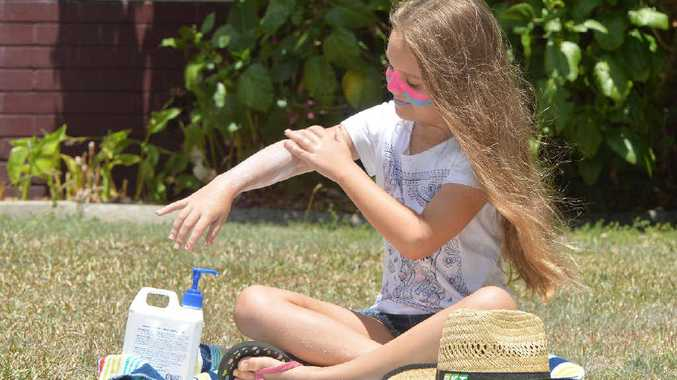 SAFE IN THE SUN: Jade McIntosh putting on sunscreen with her hat handy as she chases protection from Mackay's harsh rays. Parents are reminded to be sun smart with their children while they enjoyed the weather on their school holidays.