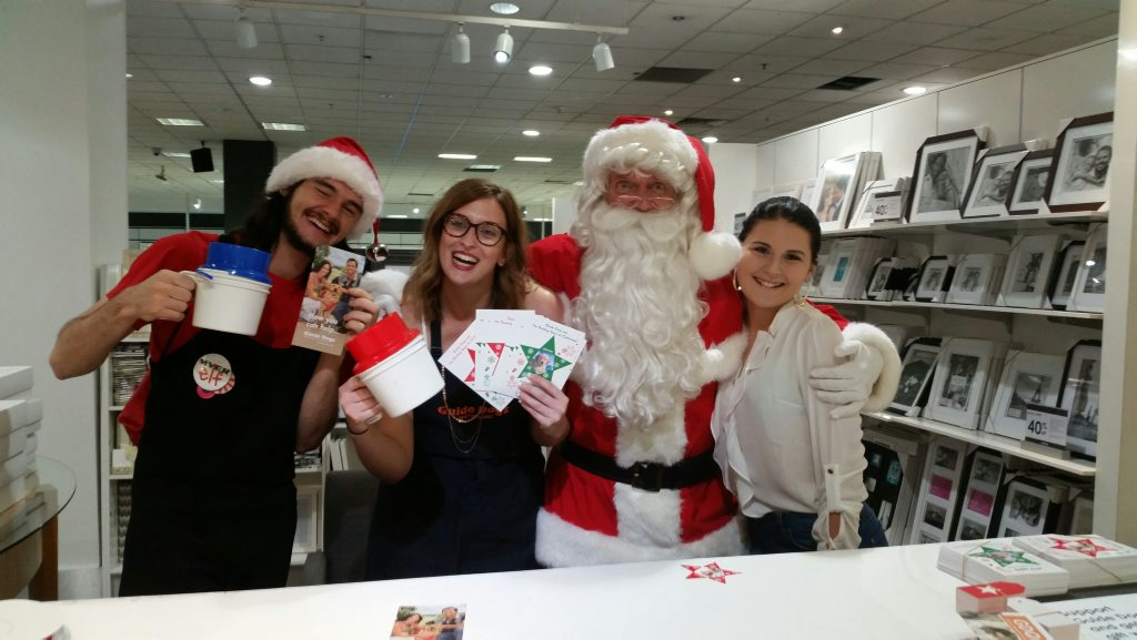 CHRISTMAS SPIRIT: Myer's Santa and his elf get behind Guide Dogs Queensland with Tayla Arthur (centre) and a young volunteer.