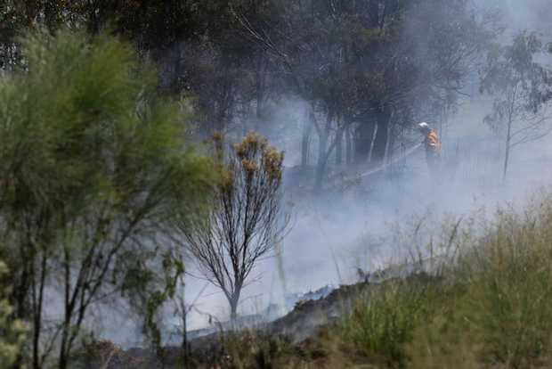 MOPPING UP: Rural fire crews hose down the site of a grass fire beside the Bunya Hwy at Taabinga.