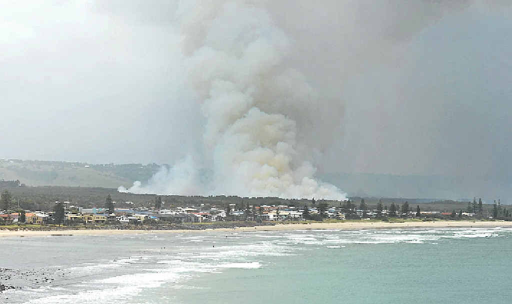 Smoke rises above Lennox Head as firefighters battle to put backburns in place around the fire burning near the Coast Rd.