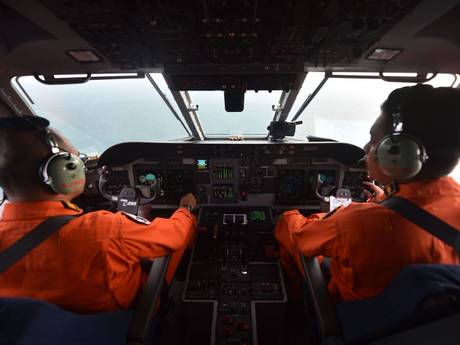 Pilot and co-pilot of the Indonesian air force keep a look out during search and rescue operations for the missing AirAsia flight QZ8501