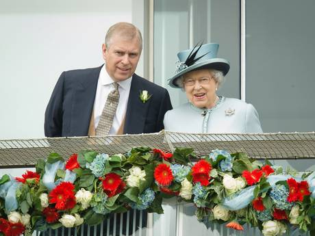 Prince Andrew, the Duke of York speaks to Queen Elizabeth II on the Queens stand during Derby day in 2013