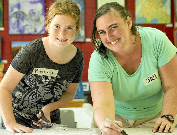 CREATIVE: Brianna Bruce, 12, and promotions co-ordinator Kristel Kelly working hard to prep tiles to be used for a mosaic.
