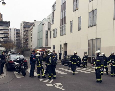 Police officers and firefighters gather in front of the offices of the French satirical newspaper Charlie Hebdo in Paris