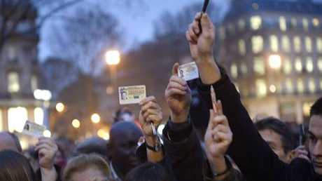 Journalists raise their press cards as others hold up pens during a vigil at the Place de la Republique