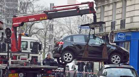 A lorry tows the car used by armed gunmen who stormed the Paris offices of satirical newspaper Charlie Hebdo