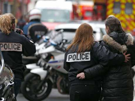 French police assist a woman after a shooting in the street of Montrouge