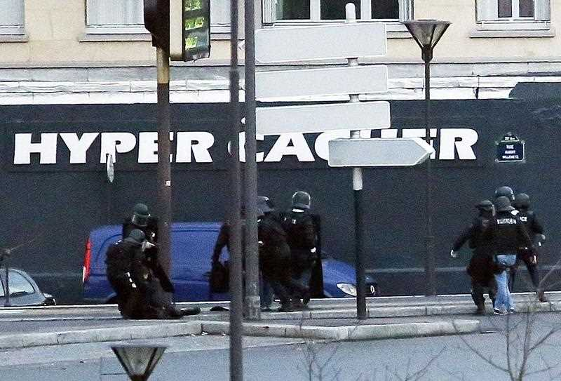 Members of the French police special forces attend to one of their colleagues lying on the ground after they launched the assault at a kosher grocery store in Porte de Vincennes, eastern Paris, on January 9, 2015 where at least two people were shot dead on January 9 during a hostage-taking drama at a Jewish supermarket in eastern Paris, and five people were being held, official sources told AFP.