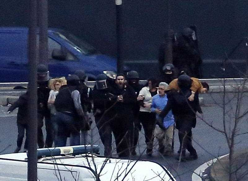 Members of the French police special forces evacuate the hostages after launching the assault at a kosher grocery store in Porte de Vincennes, eastern Paris, on January 9, 2015 where at least two people were shot dead on January 9 during a hostage-taking drama at a Jewish supermarket in eastern Paris, and five people were being held, official sources told AFP.