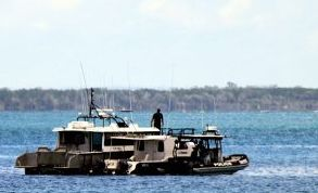 Water police tow a boat into Urangan boat harbour after a man was found dead onboard.